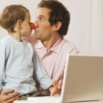 Father and son (4-5) at laptop, boy wearing clown nose
