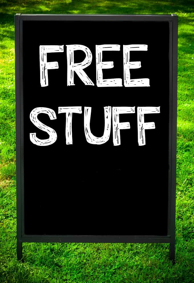 FREE STUFF message on sidewalk blackboard sign against green grass background. Copy Space available. Concept image